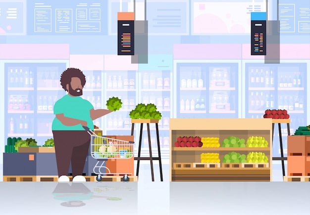 Uomo con carrello della spesa carrello scegliendo frutta e verdura ragazzo concetto cliente cliente negozio di alimentari interno orizzontale piena lunghezza