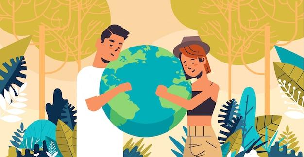 Il globo della terra della tenuta delle coppie della donna dell'uomo va verde ritratto orizzontale del fondo del paesaggio di concetto di risparmio energetico di conservazione dell'ambiente del pianeta