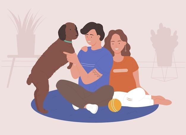 Coppia uomo e donna trascorrono del tempo e giocano con l'animale domestico a casa insieme, rilassandosi con il proprio cane all'interno