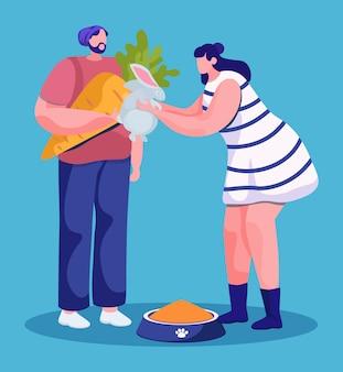 Uomo e donna che alimentano animali domestici con la carota. coppia isolata di pantaloni a vita bassa che danno verdura al coniglietto