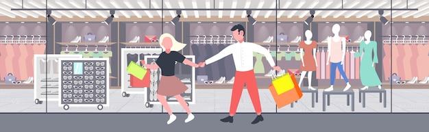 Uomo donna che tiene i sacchetti di shopping coppia divertirsi camminando insieme vacanza grande concetto di vendita moderno boutique moda negozio esterno orizzontale banner completo
