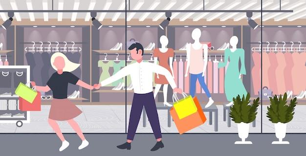 Uomo donna che tiene i sacchetti di shopping coppia divertirsi camminando insieme grande concetto di vendita boutique moderno negozio di moda moderno esterno orizzontale