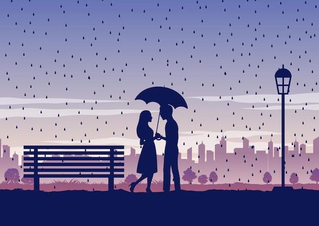 Uomo e donna con ombrello in mezzo alla pioggia