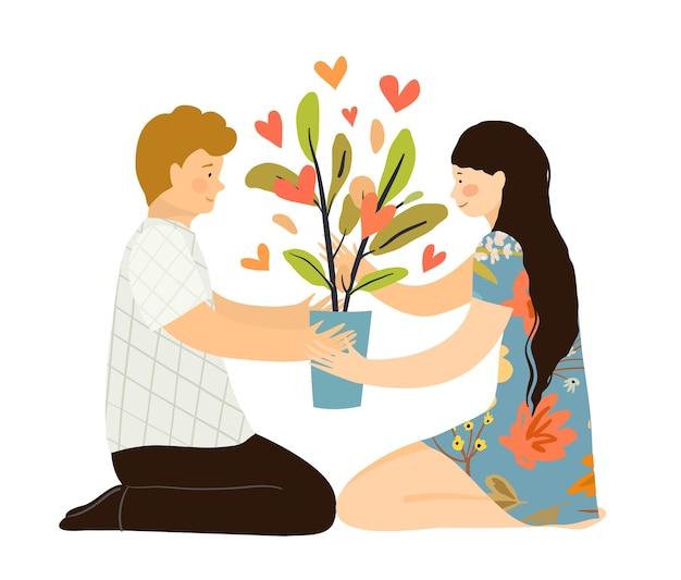 Uomo e donna innamorati seduti con una pianta d'appartamento sul pavimento, accovacciati, con in mano un vaso di fiori con la pianta dei cuori. amore crescente insieme concetto psicologico.