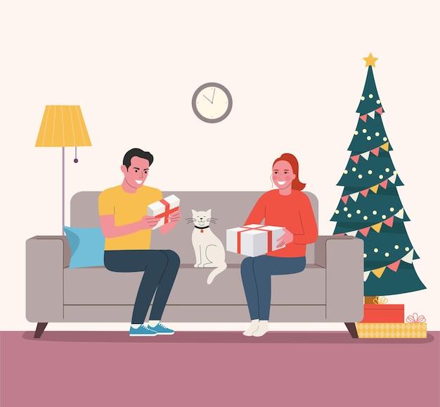 Uomo e donna che si siedono sul divano con scatole regali vicino all'albero di natale