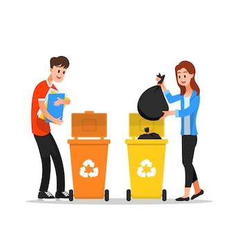 L'uomo e la donna gettano la spazzatura nei cassonetti per il riciclaggio