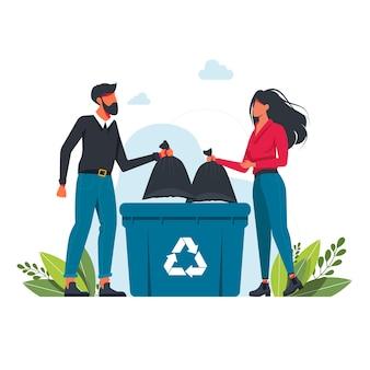 L'uomo e la donna gettano un sacco della spazzatura in un bidone della spazzatura, segno di riciclaggio dei rifiuti volontariato, ecologia, concetto di ambiente la gente getta la spazzatura nel bidone della spazzatura. concetto di pianeta pulito