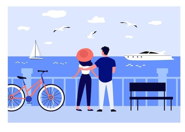 Uomo e donna che camminano sul lungomare in mare