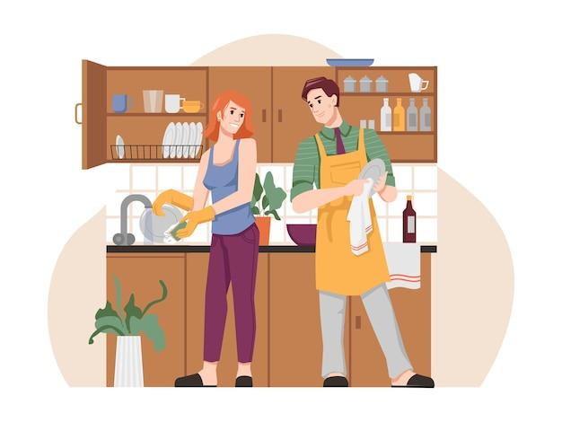 Uomo e donna che lavano e asciugano i piatti in cucina