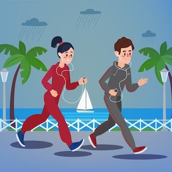 Uomo e donna con le cuffie che corrono in riva al mare