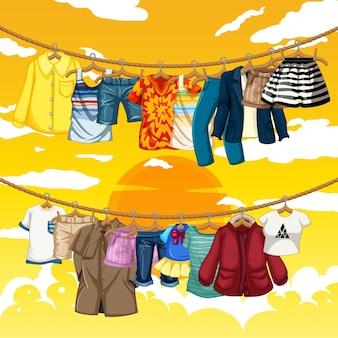 Molti vestiti appesi su una linea su sfondo giallo cielo