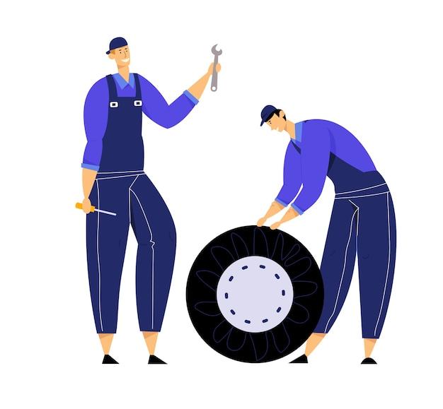 Meccanici vestiti in tuta blu che tiene la ruota di automobile