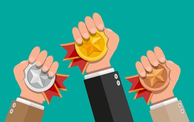 Medaglie con nastri rossi e forme a stella nelle mani. campione d'oro, d'argento, di bronzo. medaglione dei vincitori. primo, secondo, terzo posto, risultato, premio, premio, bonus badge leader. illustrazione in stile piatto