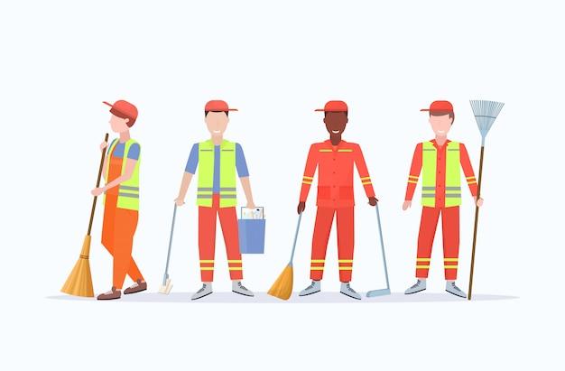 Gli uomini gli spazzini in uniforme che tiene gli strumenti differenti mescolano i lavoratori maschii della corsa che stanno insieme il fondo bianco integrale piano di concetto di servizio di pulizia orizzontale