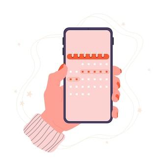 Telefono ciclo mestruale in mano con un calendario