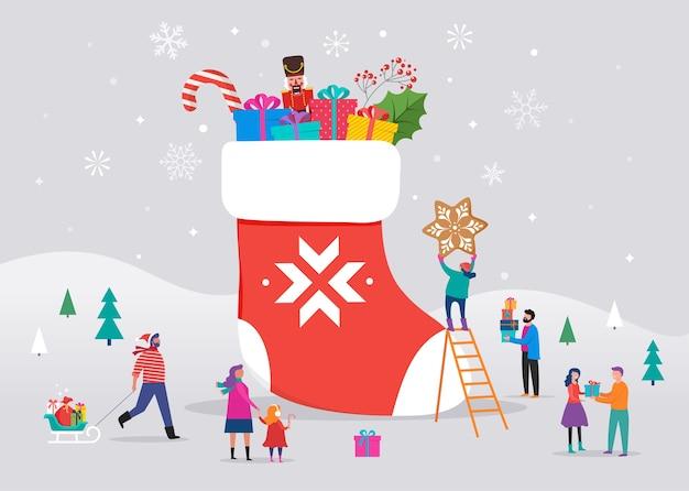 Sfondo di buon natale, scena invernale con un grande calzino rosso con scatole regalo e piccole persone, giovani uomini e donne, famiglie che si divertono sulla neve, sci, snowboard, slittino, pattinaggio sul ghiaccio