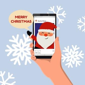 Auguri di buon natale dai social media. simpatico babbo natale sorridente. mano che tiene uno smartphone. vettore di cartone animato stile piatto.