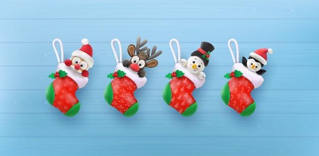 Buon natale e felice e felice anno nuovo. babbo natale, pupazzo di neve, renna e pinguino con il calzino rosso