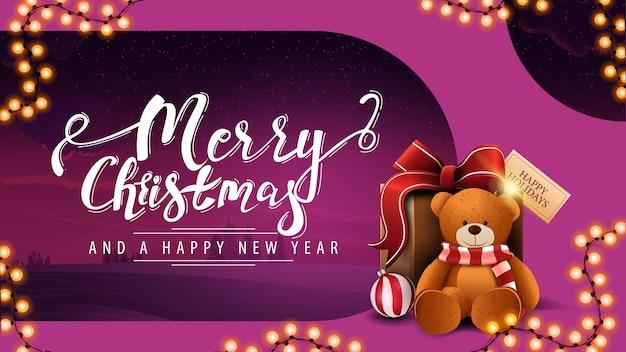 Buon natale e felice anno nuovo, cartolina moderna viola con paesaggio invernale colorato, ghirlanda, bellissime scritte e regalo con orsacchiotto