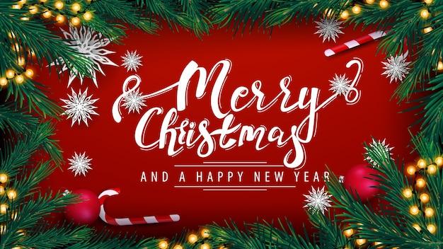 Buon natale e felice anno nuovo, cartolina rossa con ghirlanda, cornice di rami di albero di natale, palline rosse, lattine di caramelle e fiocchi di neve di carta, vista dall'alto
