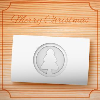 Modello dell'invito di buon natale con l'albero di abete del cartone bianco su legno