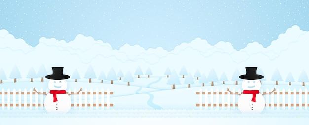 Buon pupazzo di neve di natale sull'erba e sul recinto dietro gli alberi del paesaggio invernale sulla collina e la caduta della neve