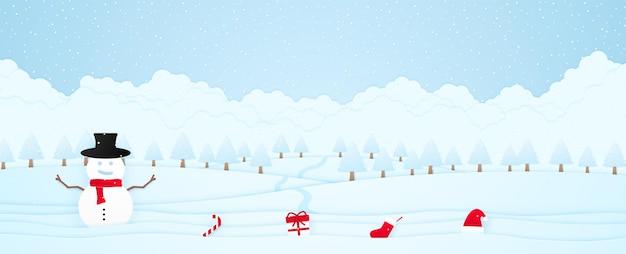 Buon natale, pupazzo di neve benvenuto e roba sulla neve, paesaggio invernale, alberi sulla collina e neve che cade, biglietto d'invito, stile arte cartacea