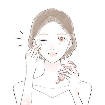 Donna di mezza età che applica la crema per gli occhi. su uno sfondo bianco.