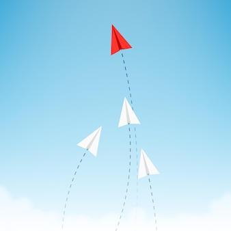 L'aeroplano di carta rosso in stile minimalista mostra la direzione per quelli bianchi.