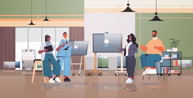Mescolare gli imprenditori della corsa che fanno la presentazione nel concetto di lavoro di squadra riunione d'affari del centro di coworking