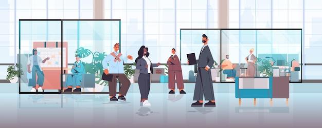 Mescolare gli imprenditori della corsa che lavorano e parlano insieme nel concetto di lavoro di squadra riunione di lavoro del centro di coworking