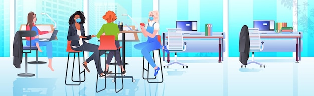 Mescolare donne d'affari di razza in maschere che lavorano e parlano insieme nel centro di coworking coronavirus pandemia lavoro di squadra concetto moderno ufficio interno orizzontale