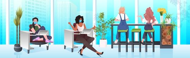 Mescolare donne d'affari di razza in maschere che lavorano insieme nel centro di coworking coronavirus pandemia lavoro di squadra concetto moderno ufficio interno orizzontale