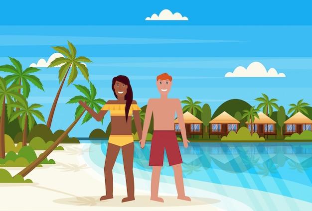Mescolare coppia gara sull'isola tropicale con villa bungalow hotel sulla spiaggia mare verde palme paesaggio vacanze estive piane