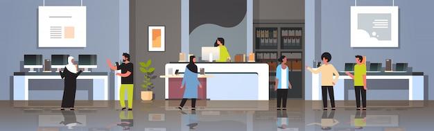 Mescolare i clienti di razza nel moderno negozio di tecnologia visitatori interni che scelgono il computer portatile schermo dello smartphone smartphone elettronica mercato piatto orizzontale