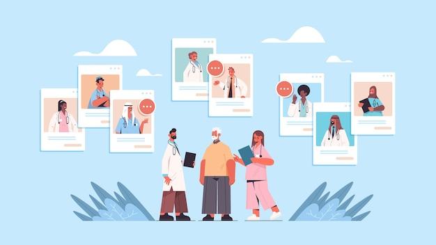 Mescolare medici di razza nelle finestre del browser web che consultano la medicina sanitaria in linea del paziente maschio anziano