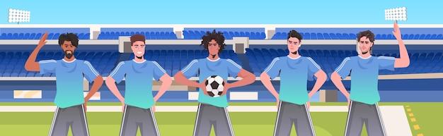 Mescolare i giocatori di calcio da corsa in piedi insieme sulla squadra di calcio dello stadio pronti per iniziare il ritratto orizzontale della partita