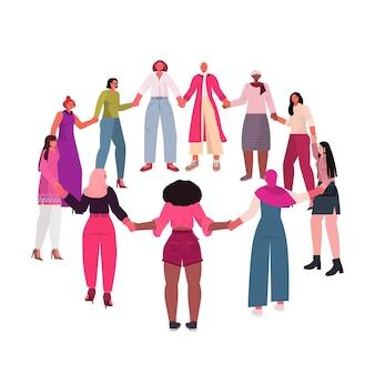 Mescolare le ragazze della corsa si tengono per mano che stanno insieme il movimento di empowerment femminile concetto di potere delle donne isolato