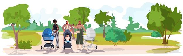 Mescolare le madri di razza che camminano con i neonati in passeggini concetto di maternità parco urbano paesaggio sfondo