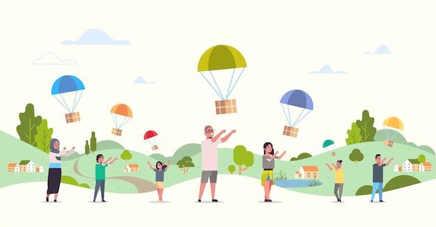 Mescolare la gente di razza che cattura la scatola del pacco che cade con il paracadute dal cielo pacchetto di spedizione posta aerea espresso paesaggio postale consegna campagna