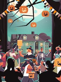 Mescolare persone di razza in costumi che camminano in città dolcetto o scherzetto felice celebrazione di halloween concetto di quarantena del coronavirus ritratto verticale