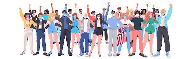 Mescolare gente di razza folla in maschere con le mani alzate in piedi insieme