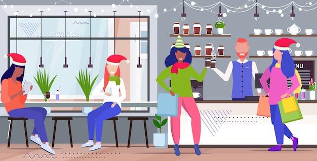 Mescolare persone di razza che bevono caffè uomini donne in cappelli di babbo natale discutendo durante la riunione interni moderni caffè schizzo a figura intera orizzontale