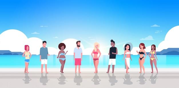 Gruppo di persone di razza mista in vacanza estiva al mare spiaggia alba