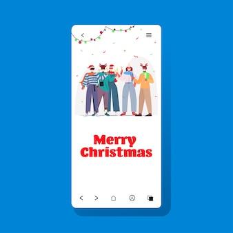 Mescolare persone di razza in maschere che celebrano il capodanno vacanze natalizie concetto di quarantena del coronavirus illustrazione dello schermo dello smartphone