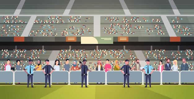 Gruppo di ufficiali di polizia di razza mista che controlla la folla di tifosi sull'arena dello stadio sportivo al supporto di sicurezza del campionato di partite di calcio