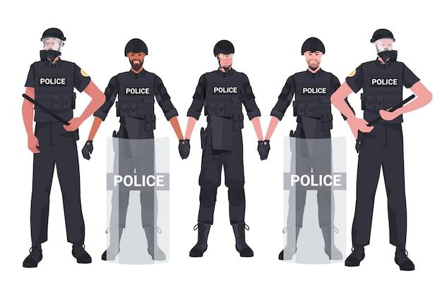 Mescolare poliziotti di razza in completo equipaggiamento tattico in piedi insieme a manifestanti poliziotti antisommossa