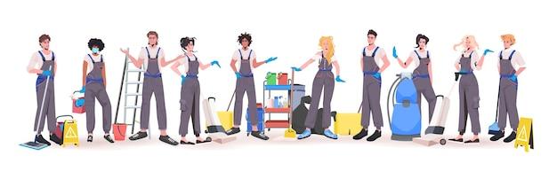 Mescolare gara professionale squadra di pulizie ufficio in piedi insieme bidelli in uniforme con attrezzature per la pulizia orizzontale