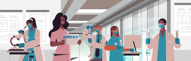 Mescolare scienziati della razza in maschere che lavorano con il dna in provette team di ricercatori che fanno esperimenti in laboratorio test del dna diagnosi di ingegneria genetica