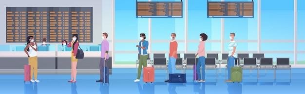 Mescolare i viaggiatori di razza con i bagagli che indossano maschere per prevenire l'interno del terminal aeroportuale della pandemia di coronavirus